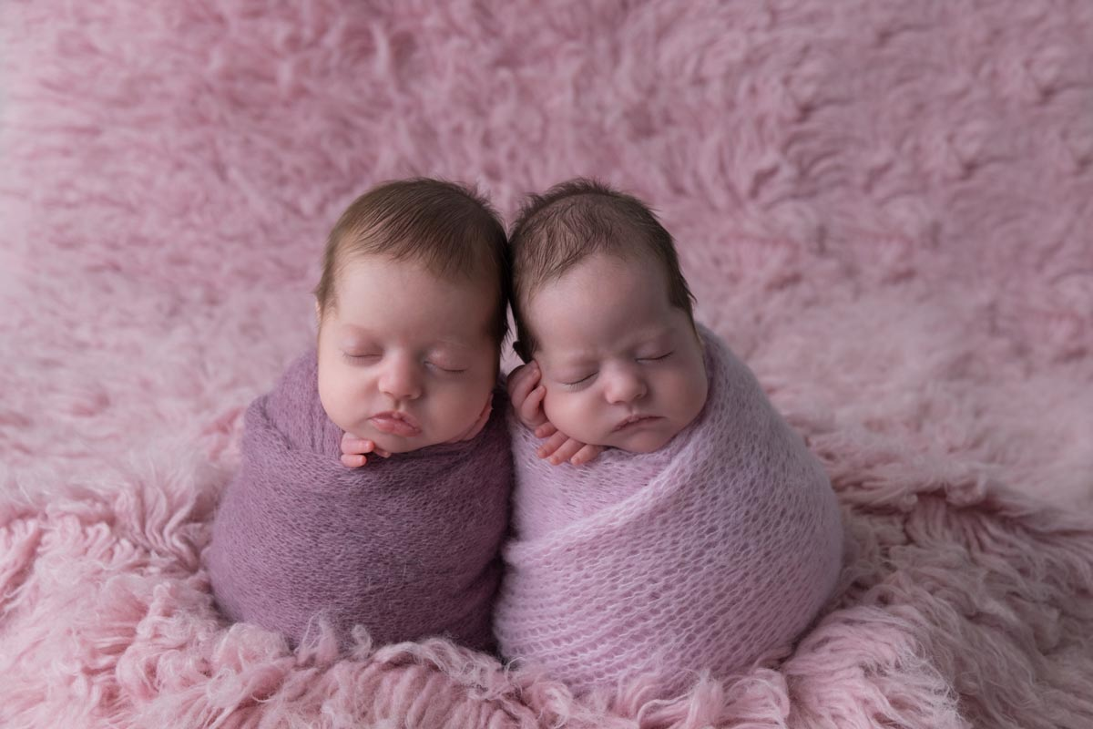 Newborn twins wrapped during the photoshoot