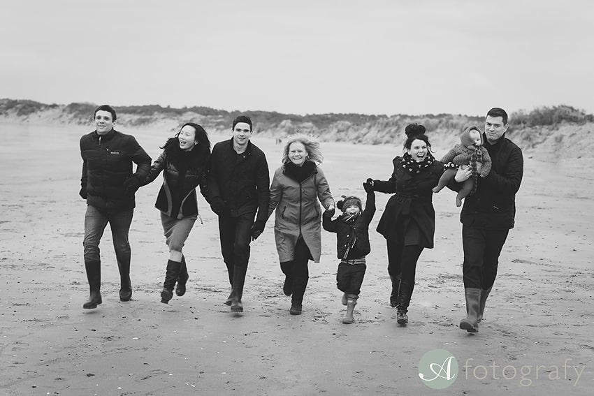 Family running on the beach to relax for the photoshoot.