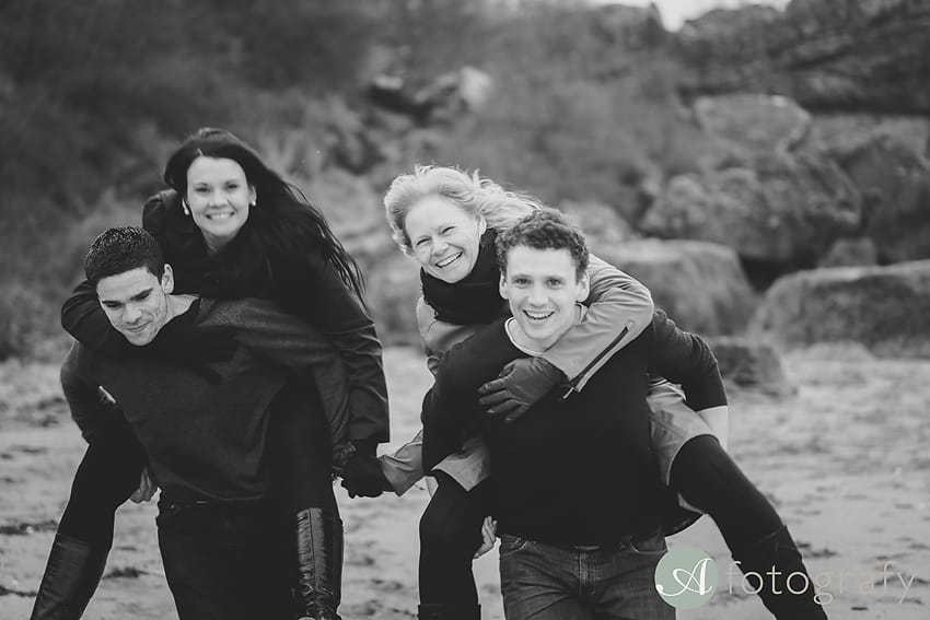 Family running on the beach while being piggyback on each other. Natural professional family photos ideas