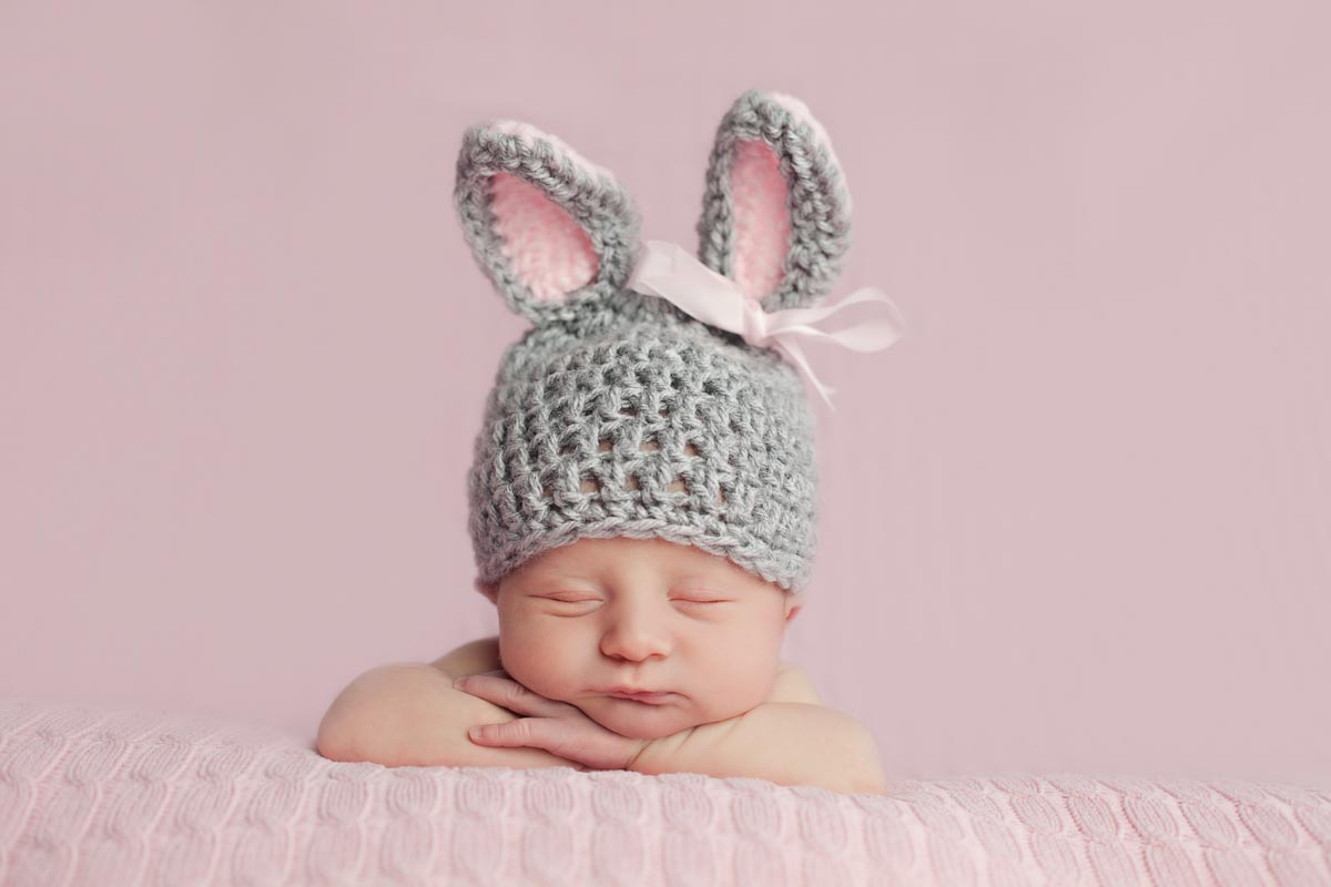 newborn baby girl wearing a bunny hat.