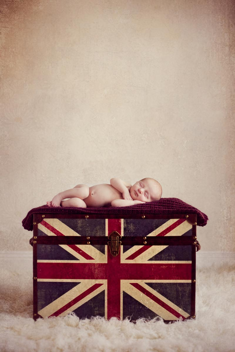 newborn baby girl sleeping on the UK union jack design box