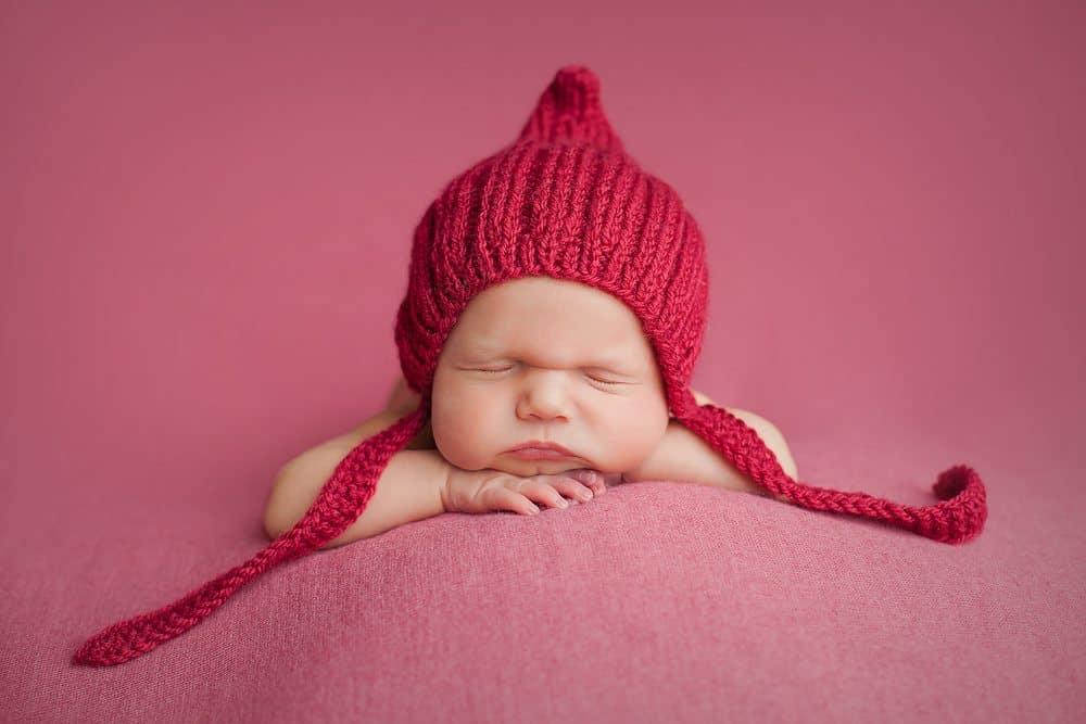 Newborn baby girl wearing red bonnet hat