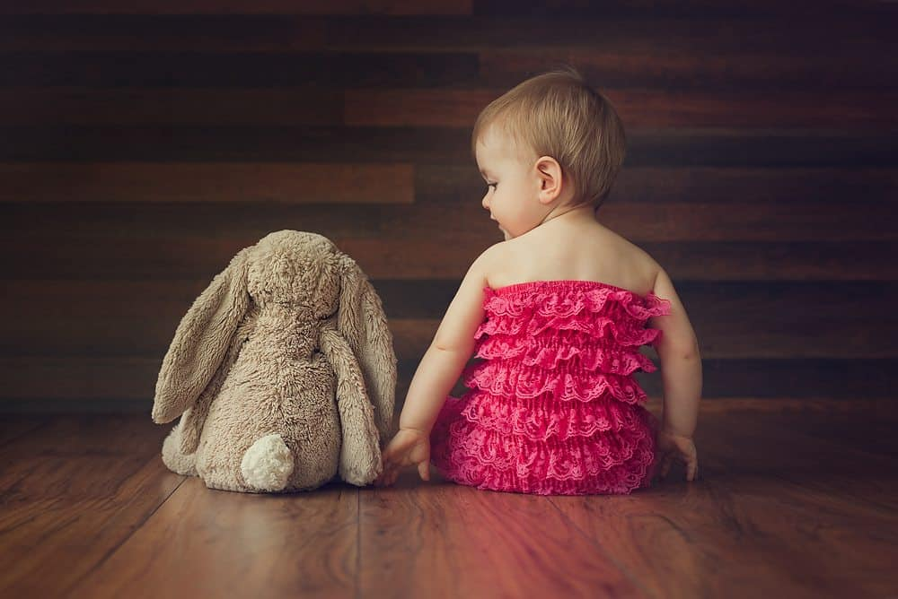 baby sitting on dark background in pink outfit with bunny beside baby