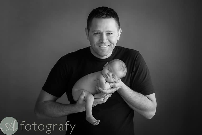 dad is holding newborn baby girl. black and white portrait