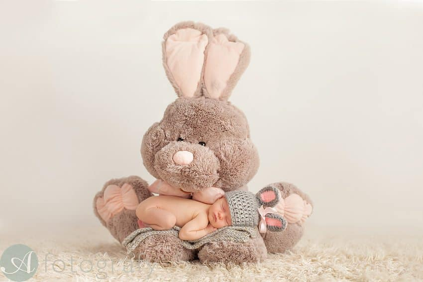 big soft toy bunny holding newborn baby with knitted bunny hat