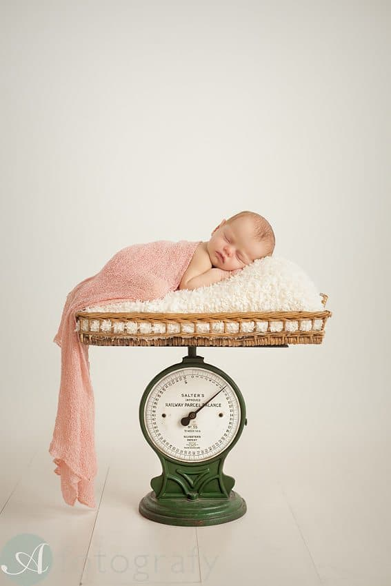 newborn girl sleeping on scales in edinburgh studio.