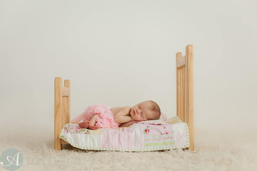 little newborn baby size bed with baby sleeping in bed.