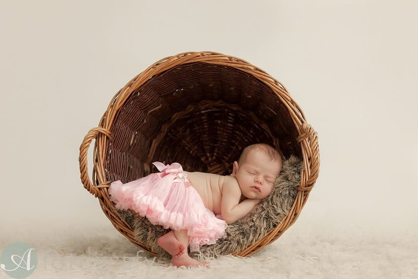 newborn baby girl wearing tutu and sleeping basket