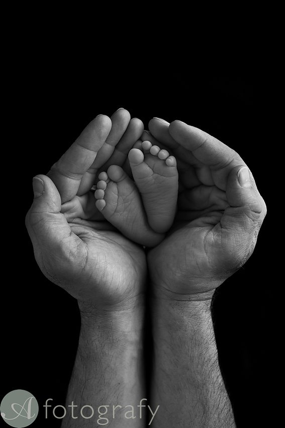 newborn feet in dadas hands