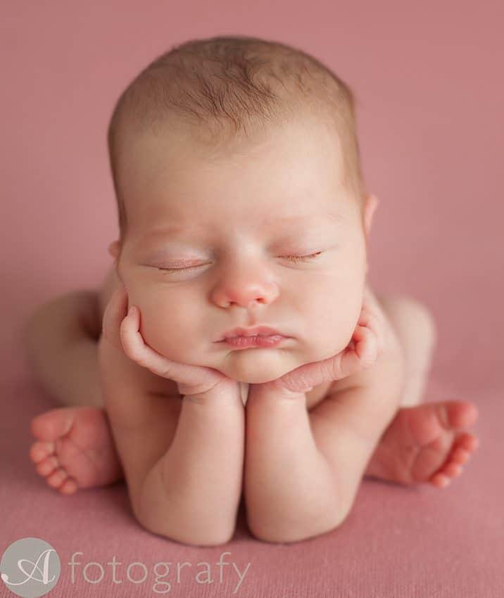 newborn girl posing in froggy pose on pink background. Advanced newborn posing.