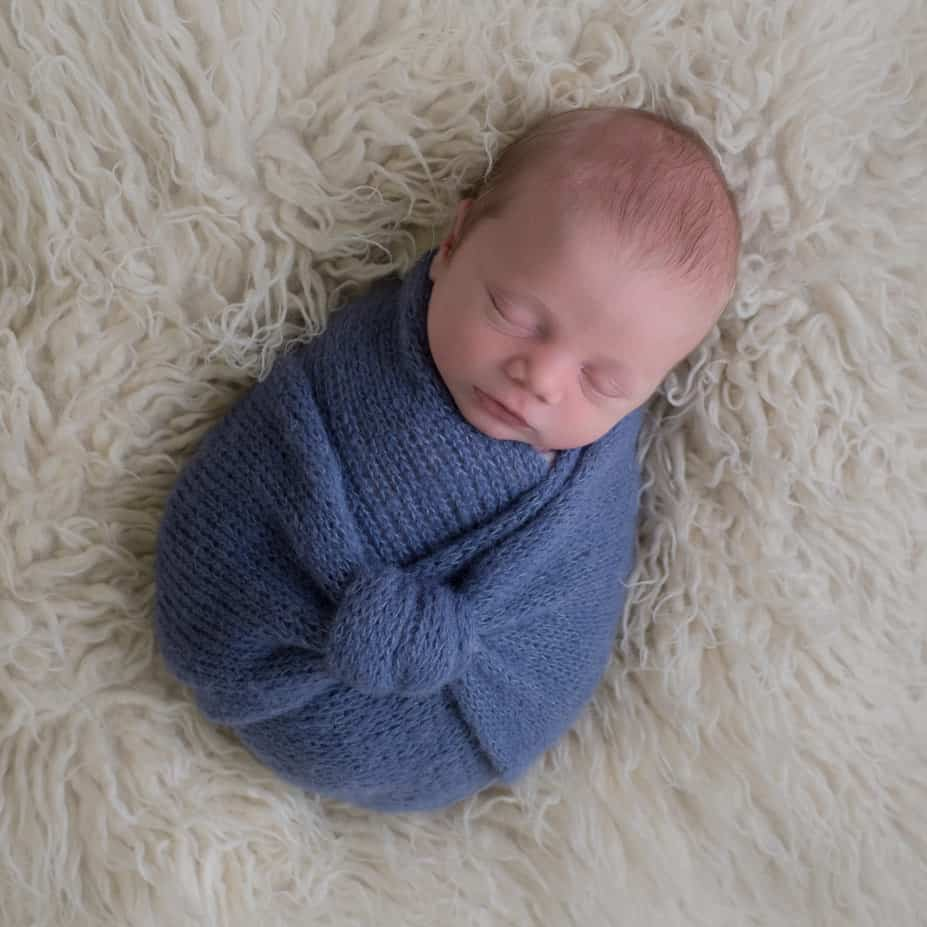newborn wrapped up in blue wrap