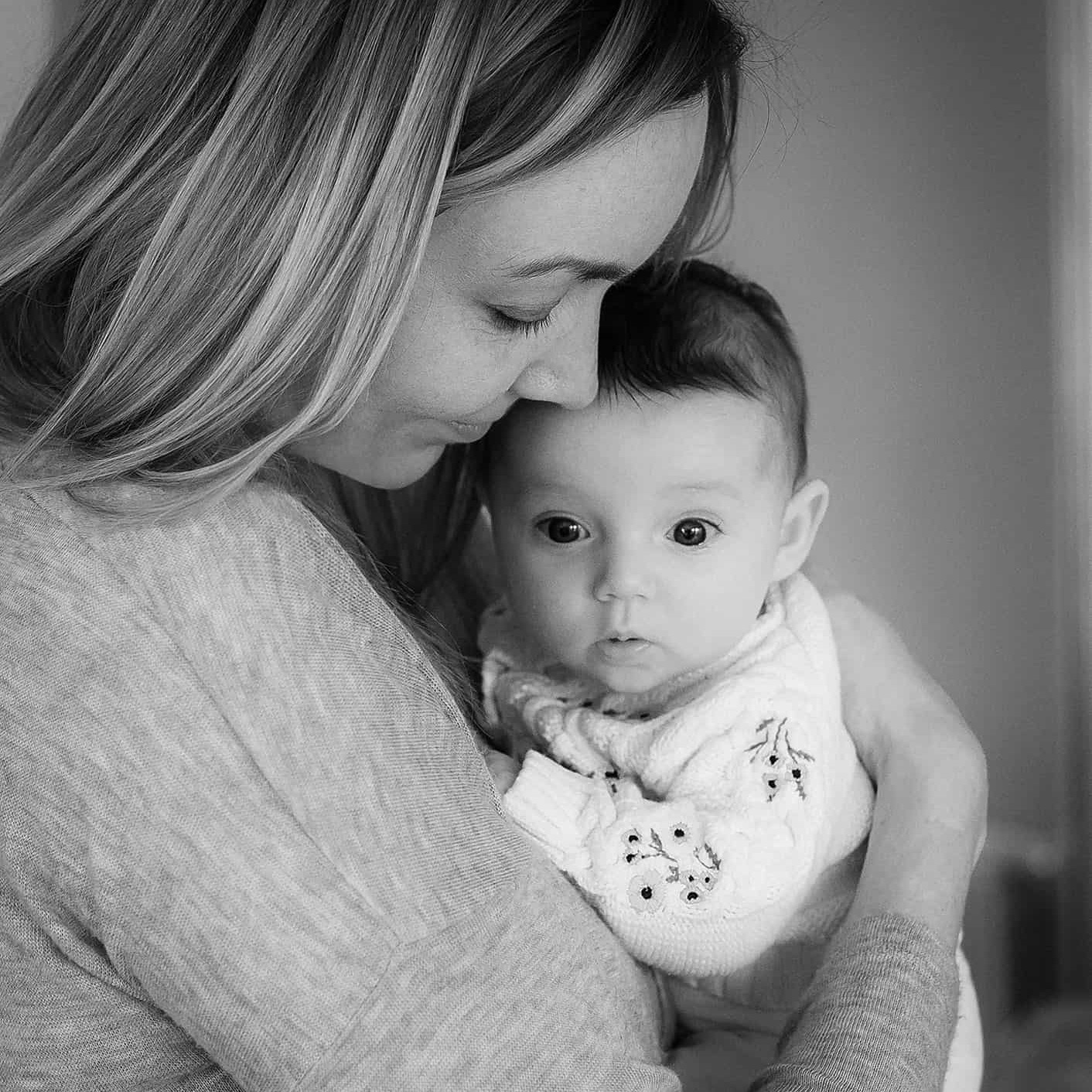 Mum holding a newborn baby during home photo session