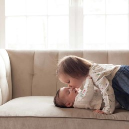 Sister is kissing her baby sister during home newborn session