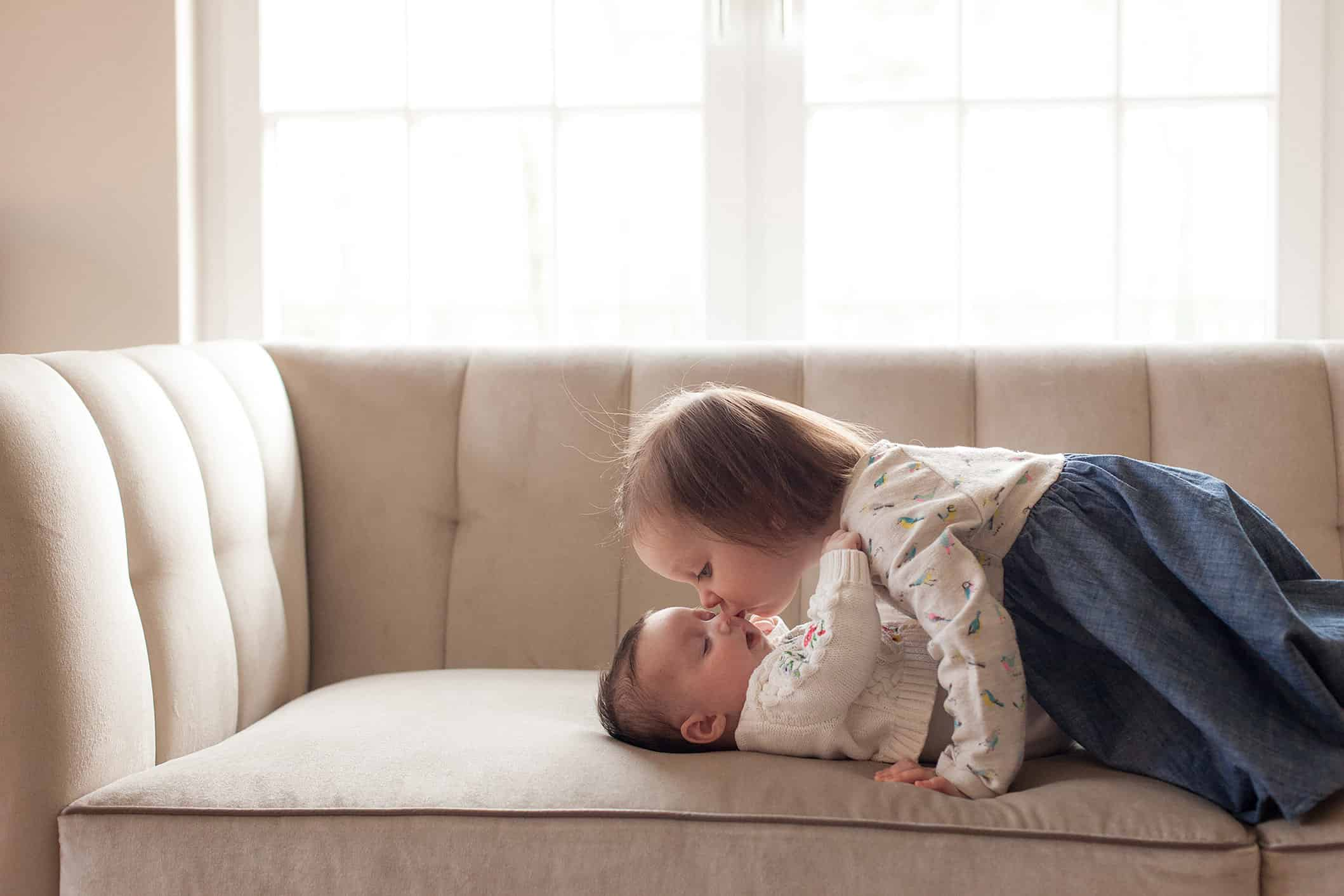 Newborn photos at home. Sister is kissing her baby sister.