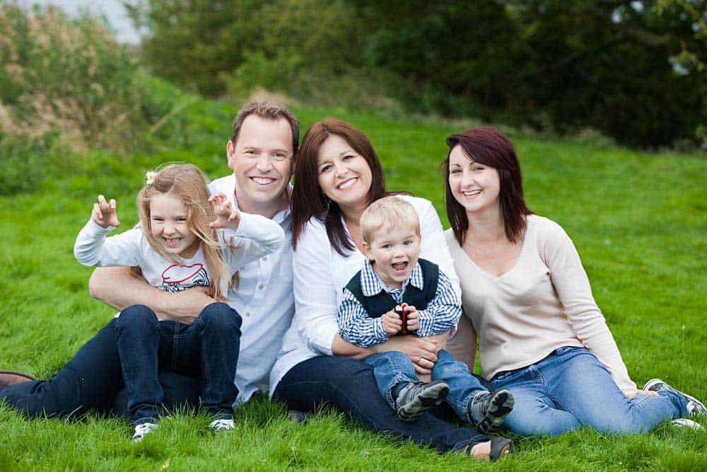 Family posing in grass during portrait photo session