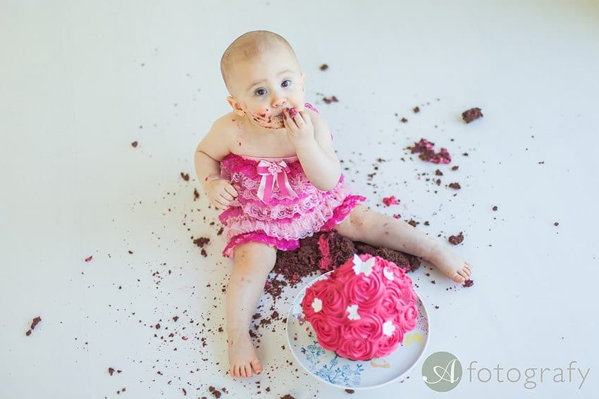 little baby girl is eating cake during the cake smash photoshoot