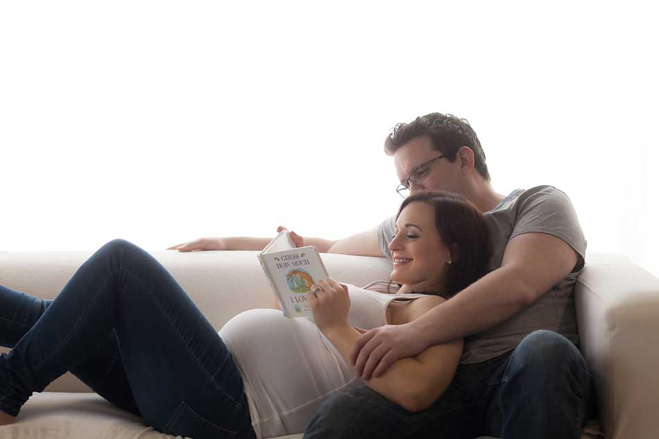 couple on sofe reading baby book during photo shoot