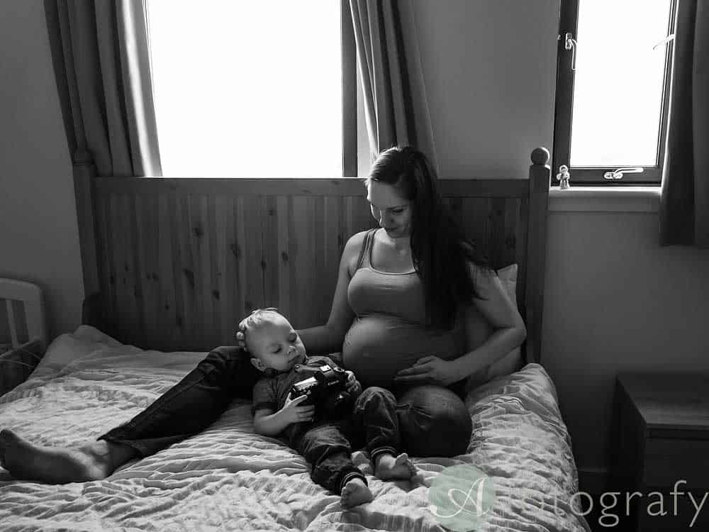 candid maternity photo with baby and mum during pregnancy session at home