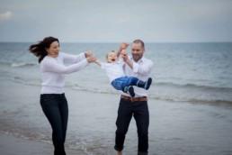 family having fun during photoshoot on the gullane beach
