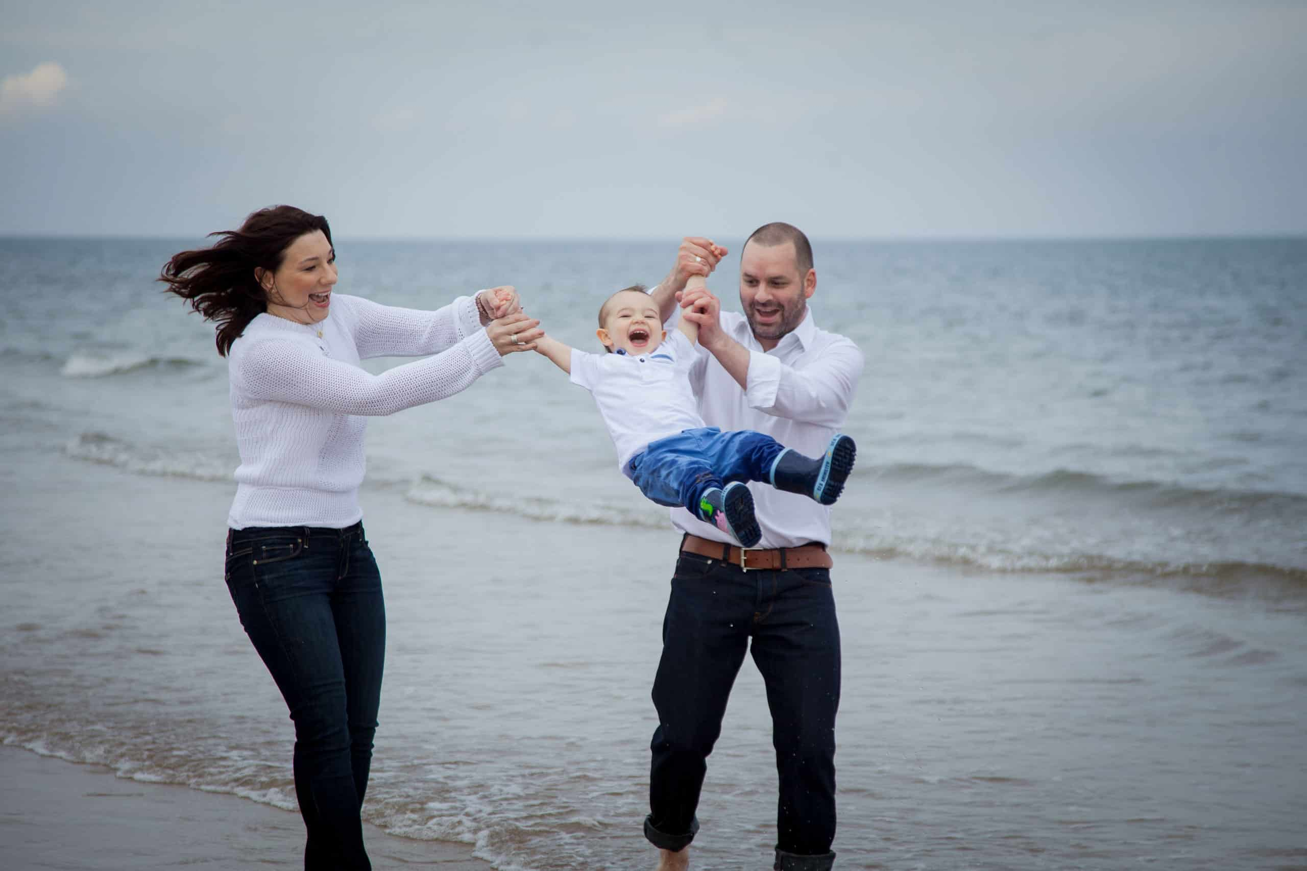 family having fun during photoshoot on the gullane beach