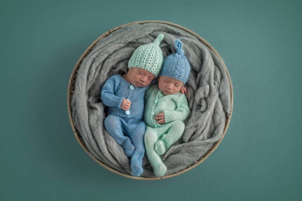 newborn twins in round basket wearing knitted outfits