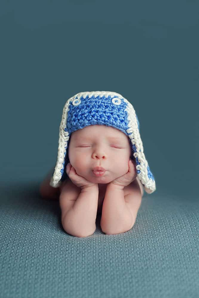 newborn baby with blue hat in head in hands pose