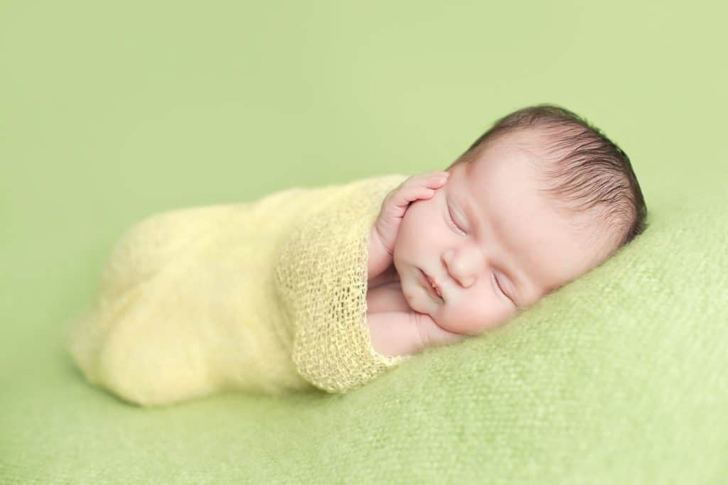 newborn wrapped in yellow wrap on green blanket during photo shoot