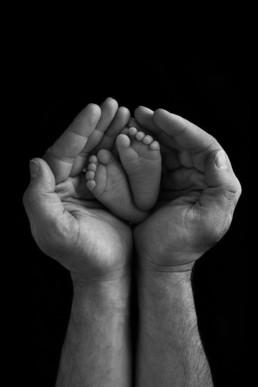 newborn photo of feet in dads hands