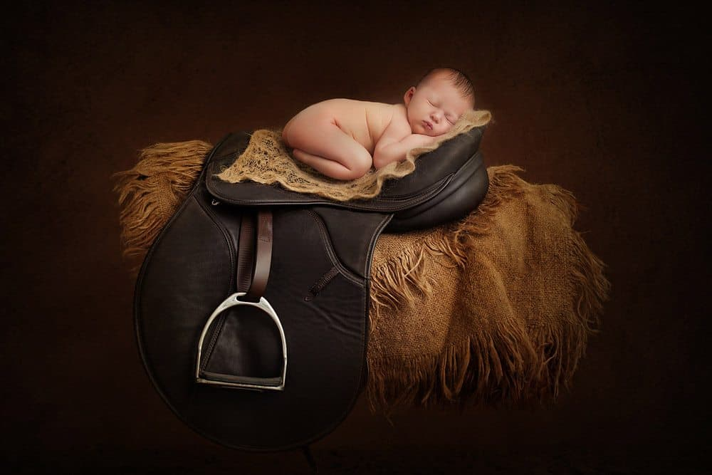 Unique newborn baby photography on horse saddle vintage