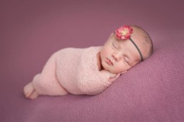 newborn girl wrapped in pink wrap wearing headband during photo shoot