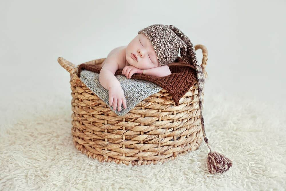 light natural light newborn portrait with long hat and in basket