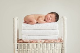 newborn baby girl on stack of towels