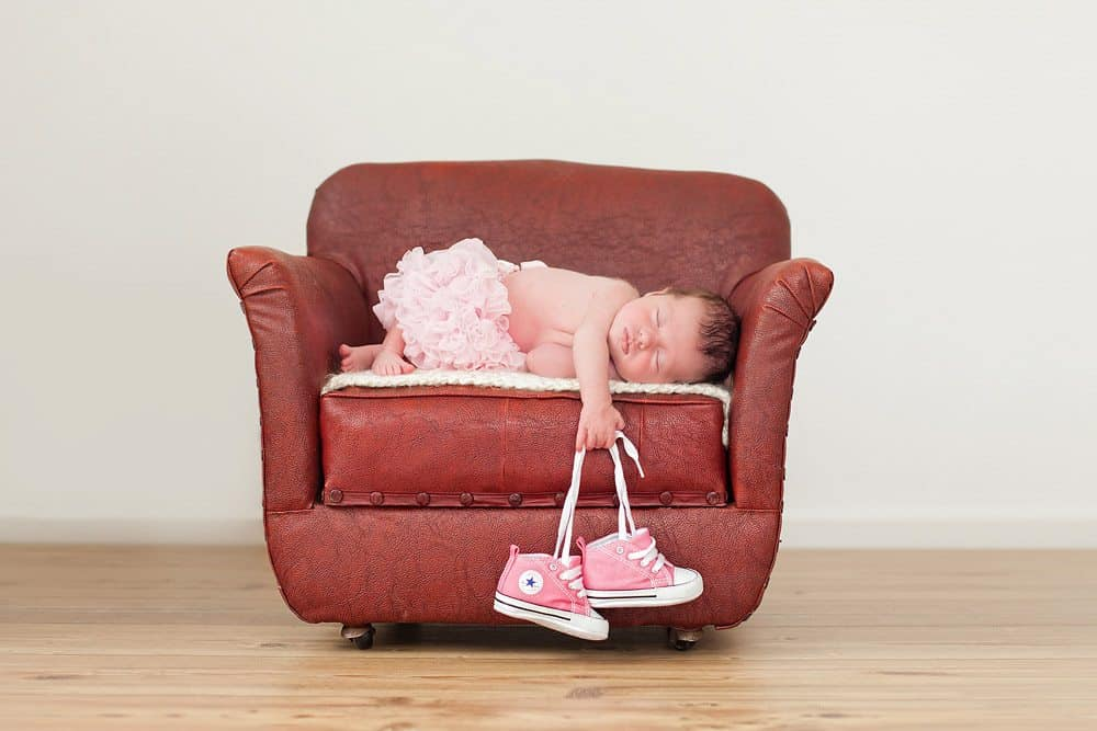 newborn baby girl holding shoes during photo session.