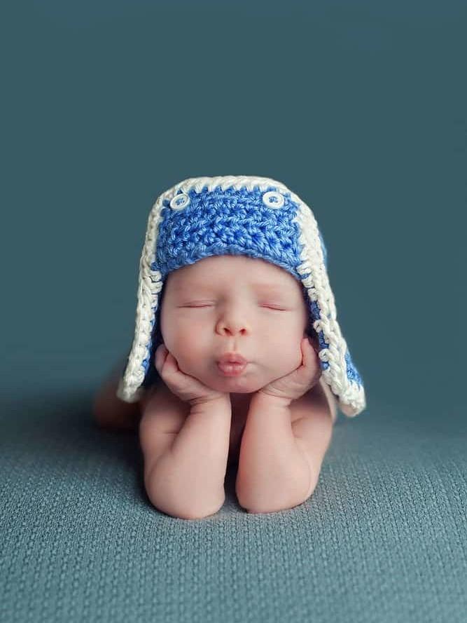 Head in hands newborn baby boy pose on the blue blanket