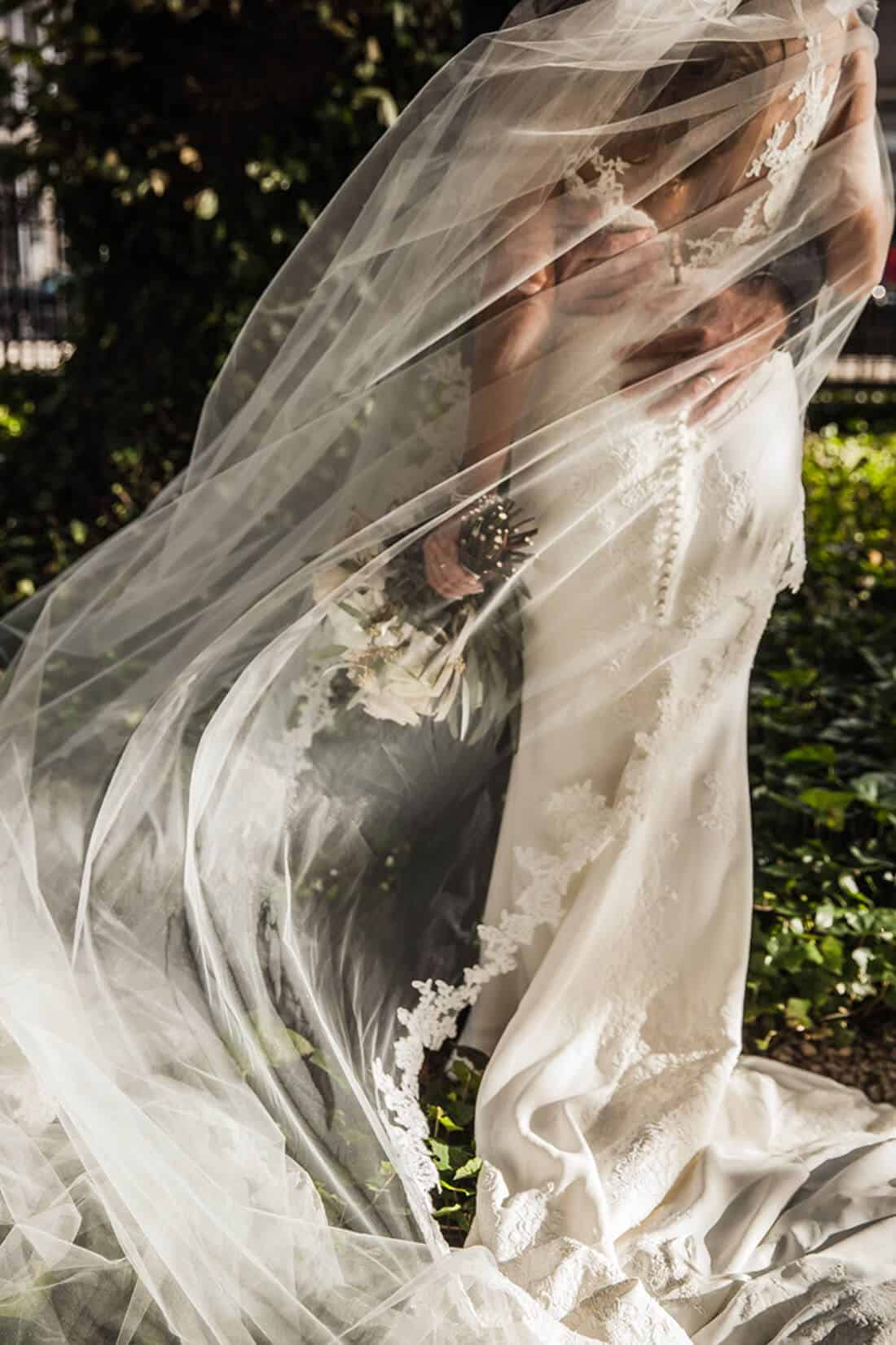 wedding couple wrapped in the veil