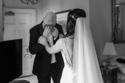 bride meets her dad after getting ready in the dres