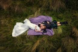 Wedding couple lay in the grass while Edinburgh wedding photographer Armands takes photos