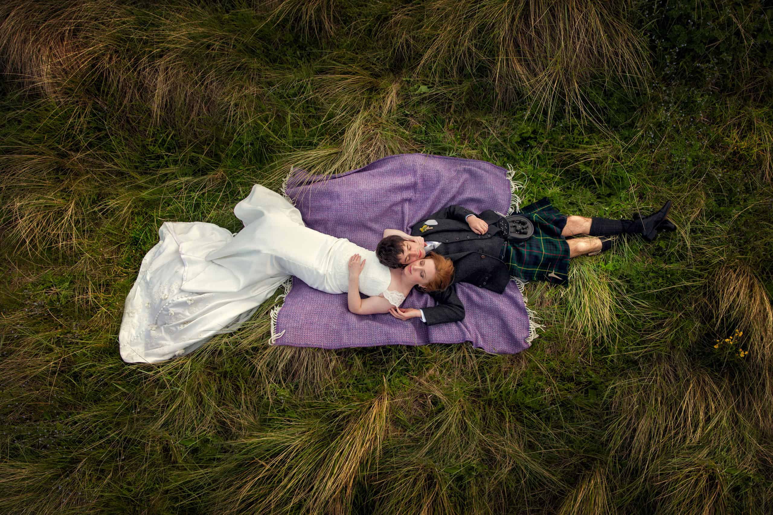 Wedding couple lay in the grass while Edinburgh wedding photographer Armands takes photos