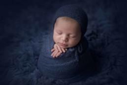 newborn baby wrapped in potato sack pose