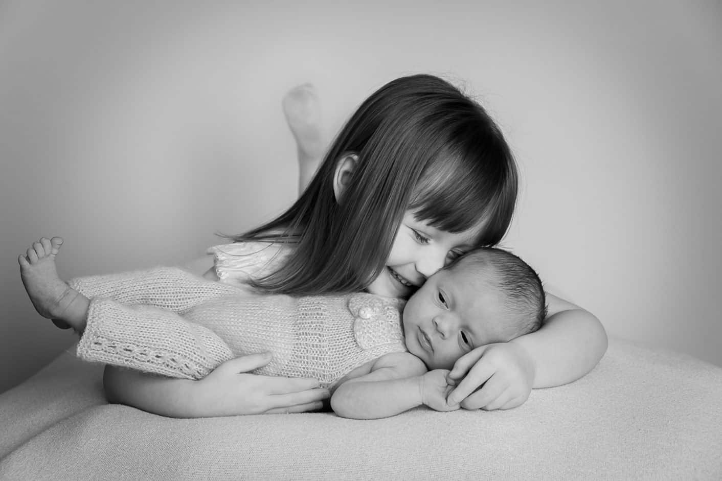 Newborn and sibling sister cuddle for the studio photo in Edinburgh