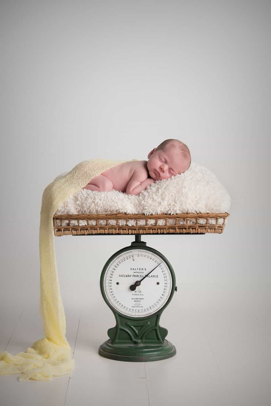 newborn baby on the scales done by edinburgh best newborn photographer