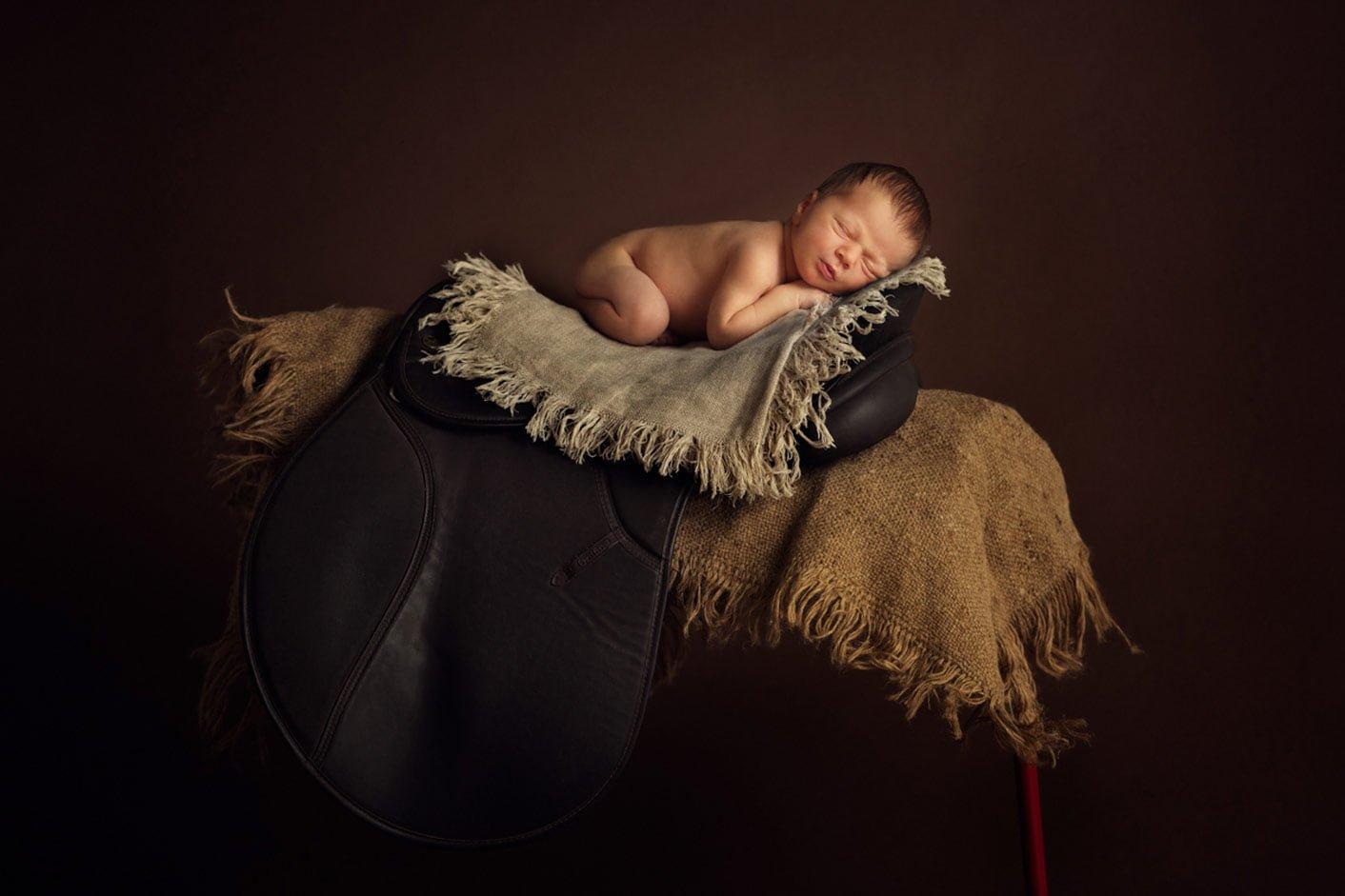 Newborn baby on the horse saddle.