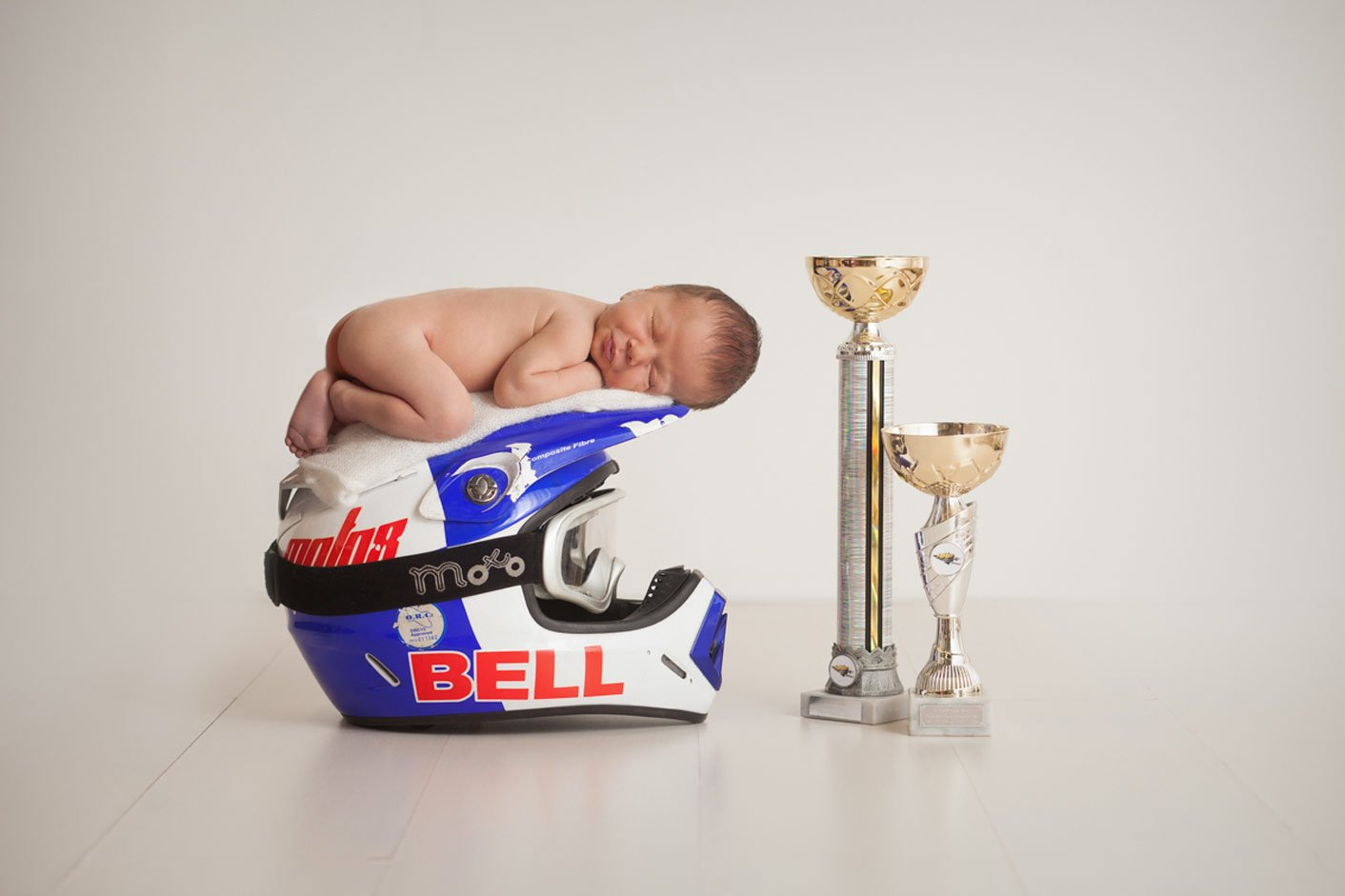 Newborn baby on the racing helmet